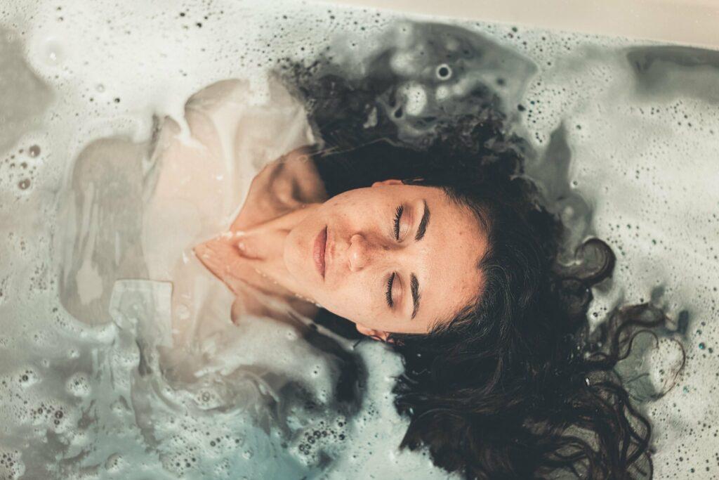 vrouw krullend haar badkuip