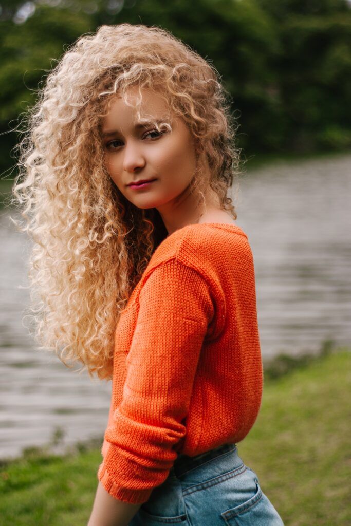 curly-haired-blond-woman-in-orange-shirt-glancing-at-her